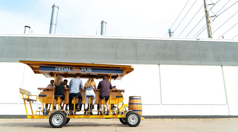 people ride on a pedal pub bike with building in background