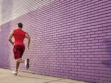 man running against purple wall