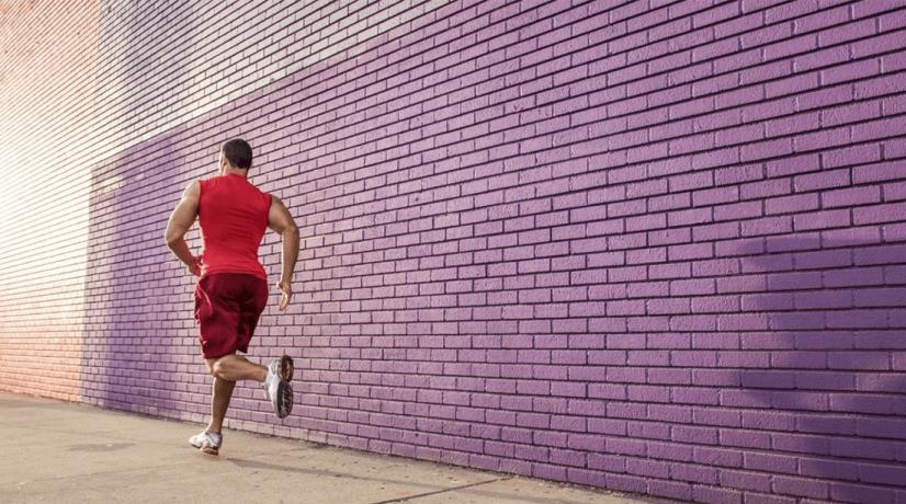 man running against purple wall