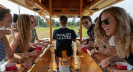guests leaning over pedal pub bike counter
